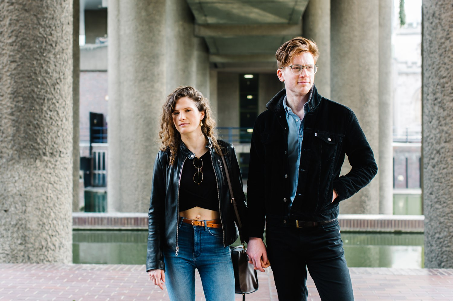 An engaged couple look in opposite directions at The Barbican in London