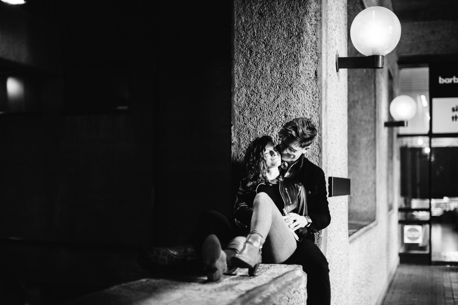 Romantic couple cuddle on a wall at The Barbican in London