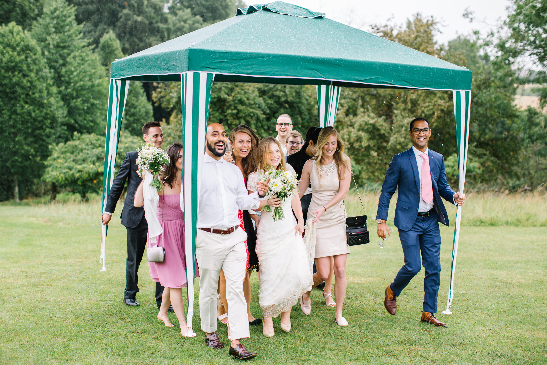 how to plan a back garden wedding bride and guests walk underneath a gazebo in the rain