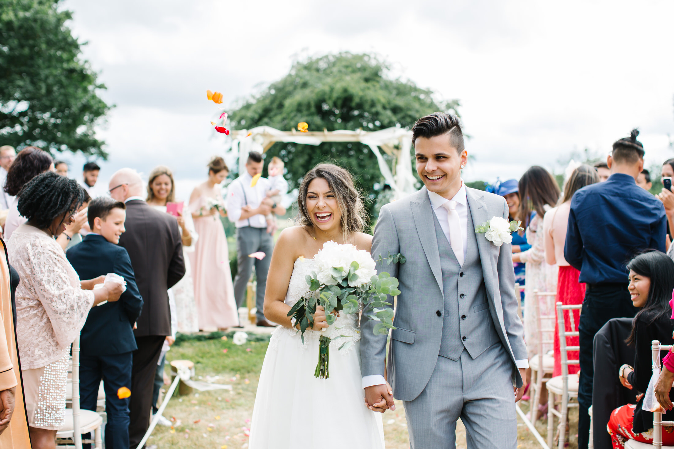 how to plan a back garden wedding bride and groom walk down aisle with confetti laughing