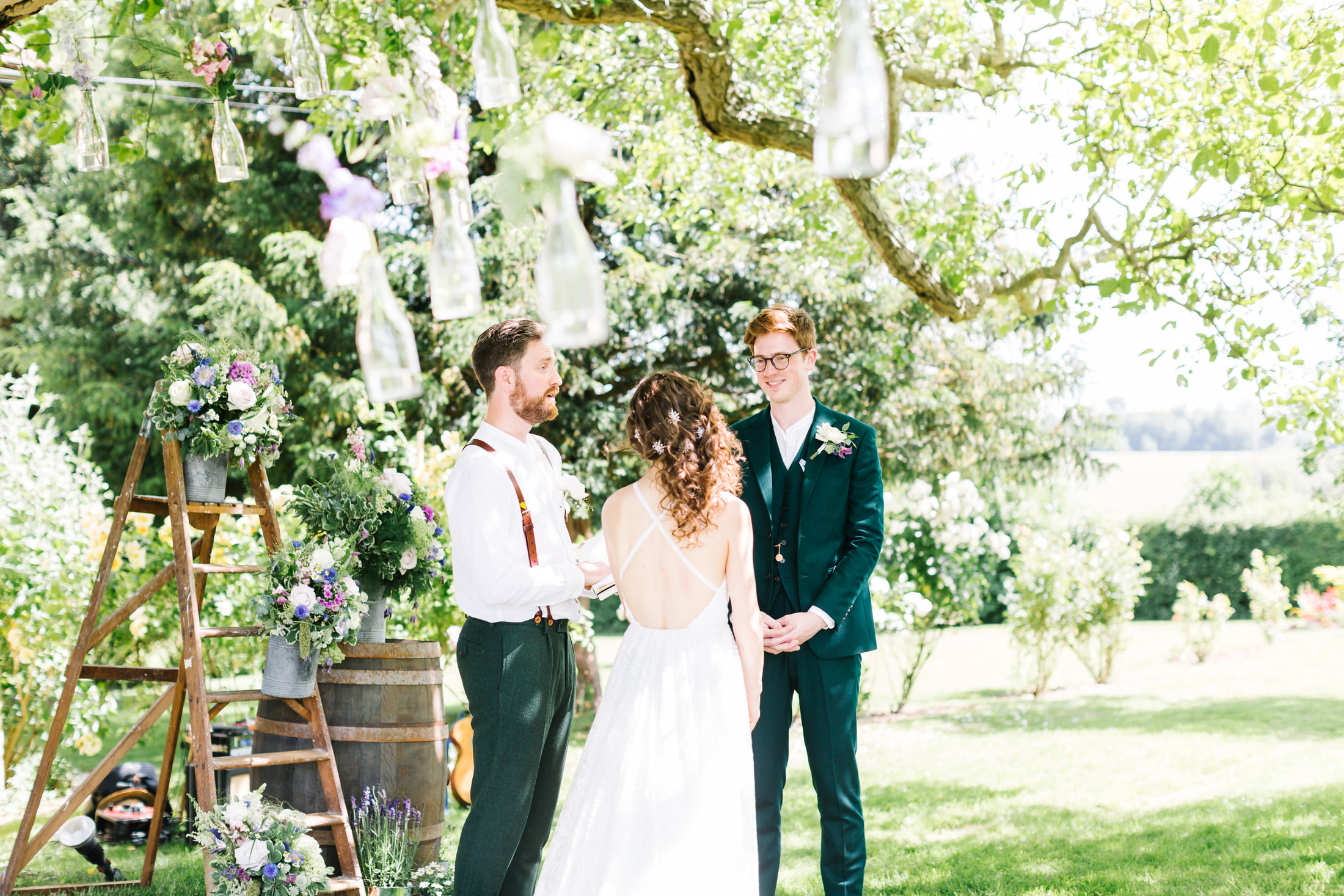 how to plan a back garden wedding bride and groom stand underneath a tree during their ceremony exchanging vows