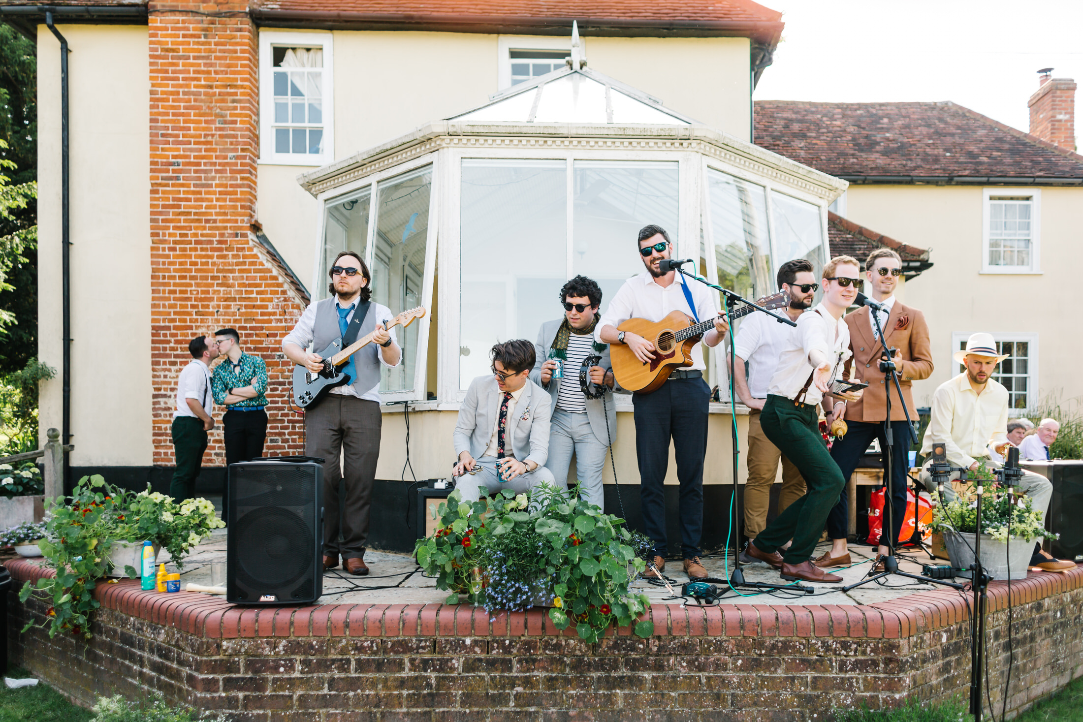 how to plan a back garden wedding guests and groomsmen play music in front of house