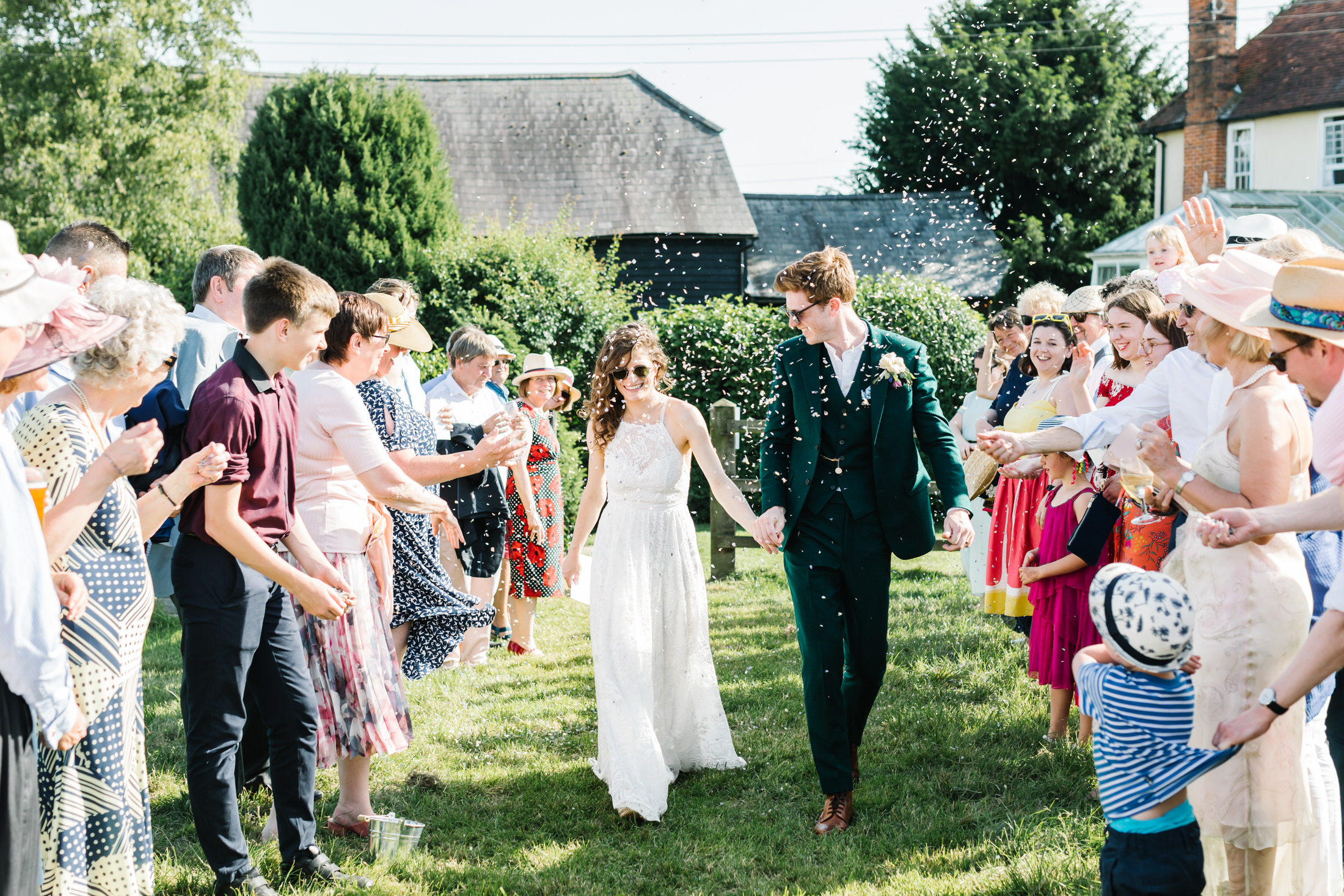 how to plan a back garden wedding bride and groom couple walk through confetti in their garden wearing sunglasses