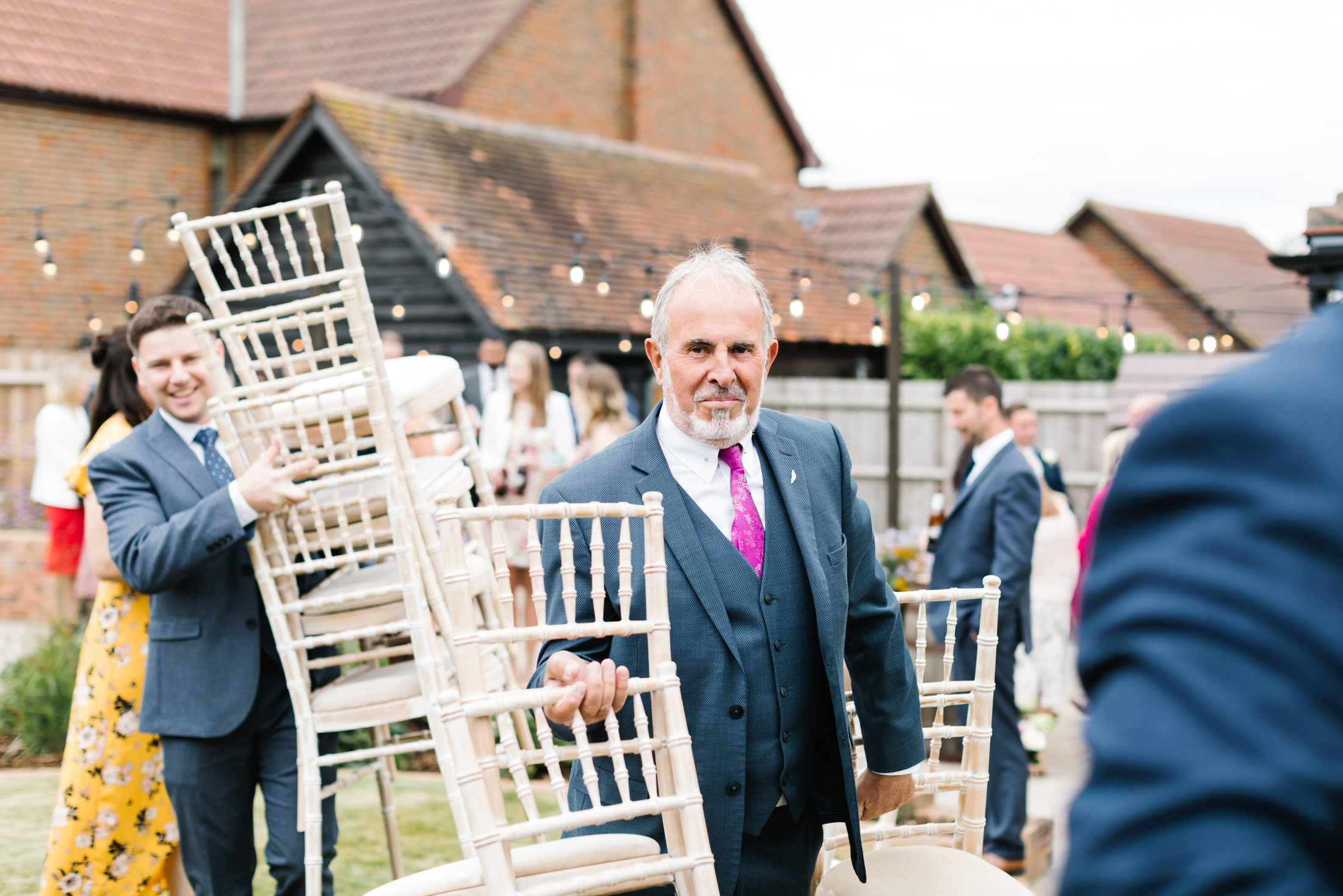 how to plan a back garden wedding guests carrying chairs after a garden ceremony